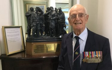 Bob Wade at the RAF Club, London, with a maquette of the Bomber Command sculpture in Green Park.