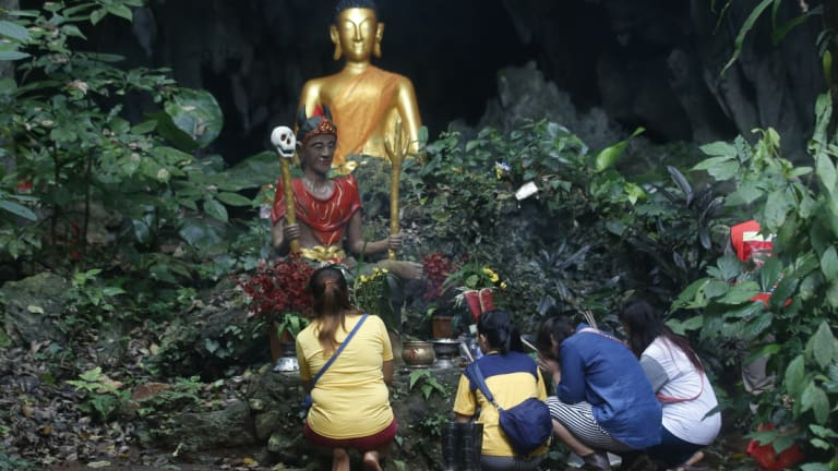 Family members pray in front of a Buddhist statue near a cave where 12 boys and their soccer coach have been trapped since June 23, in Mae Sai, Chiang Rai province.