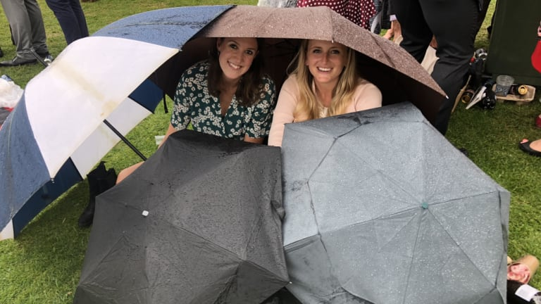 The messy aftermath Camilla Blands and Kirsten Feathers shielded themselves from the rain.