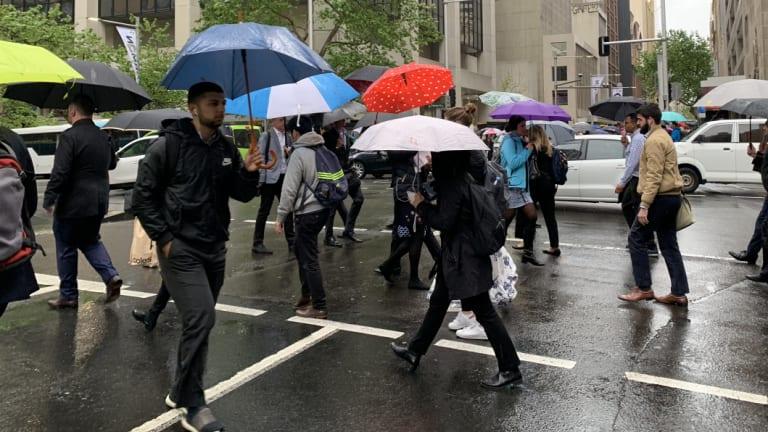 Pedestrians brave the rain in Market Street in Sydney's CBD.