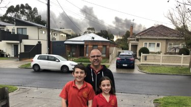 Dave Stembridge with his children Will and Isla and, behind them, the plume of smoke from the factory fire.