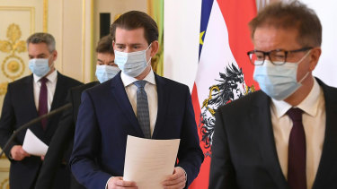 Austrian Chancellor Sebastian Kurz, centre, arrives for a coronavirus news conference with other ministers in Vienna.