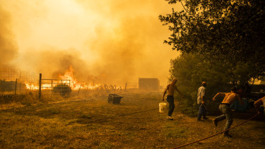 A family works to protect property as a fire approaches in Vacaville, California.