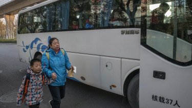 A mother brings her son to the Real Boys Club bus that will take enrolled boys to the sports school in Beijing.