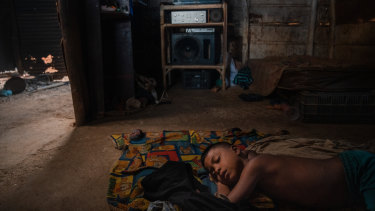 Dioger Lares, 7, fell asleep watching the television his father repaired with the money he traded for gold earrings, in Guaca, Venezuela.