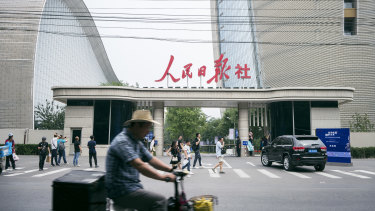 Traffic passes the west security gate of the Beijing offices of the People's Daily and the Global Times, which are both controlled by the ruling Communist Party.