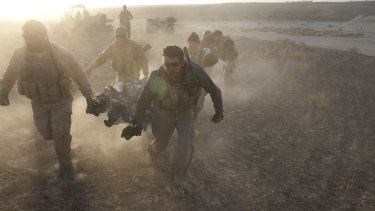 US special forces rush a wounded Afghan soldier to a helicopter of the 101st Aviation brigade in Afghanistan's southern Kandahar province in December 2010.