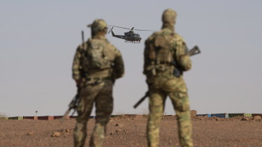 Canadian soldiers watch as a Canadian helicopter provides air security during a demonstration for Prime Minister Justin Trudeau on the United Nations base in Gao, Mali in December.