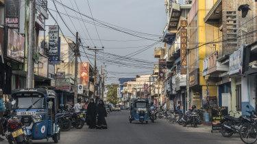 Women wearing abayas walk down a street in Kattankudy, the hometown of Zaharan Hashim.