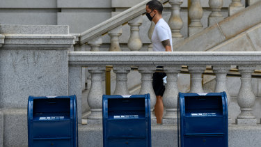 A person wearing a protective mask walks by United States Postal Service collection boxes near Capitol Hill in Washington, DC.