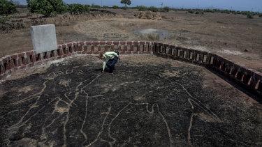 Amateur archaeologist Sudhir Risbud examines a petroglyph of an elephant.