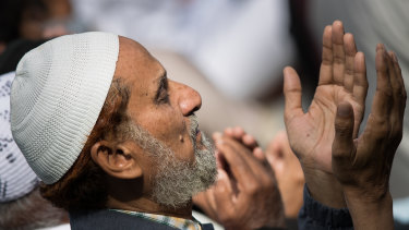 A man  prays in Hagley Park across from the Al Noor Mosque at a national call to prayer on Friday.
