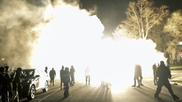 Authorities use flash bombs to disperse the crowd.