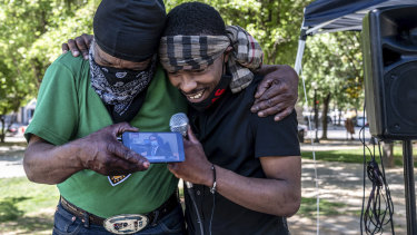 Stevante Clark, right, brother of Stephon Clark who was fatally shot by Sacramento Police, is hugged by his cousin Steven Ray Collins in Sacramento California, as they listen to the Chauvin verdict on their phone.