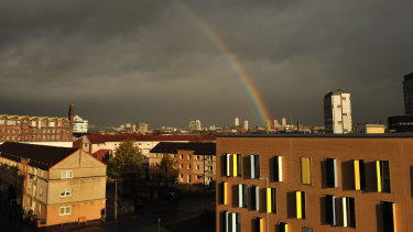 Dark brooding skies over Glasgow city centre lit up by sunshine and a rainbow.