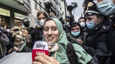 Silvia Romano, escorted by Carabinieri, lowers her face mask for press as she arrives at her home, in Milan, Italy.