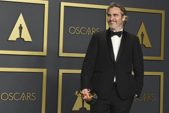 Joaquin Phoenix poses in the press room with his Oscar for best actor in a leading role.