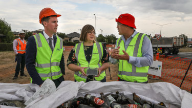Executive general manager of road services at Downer Dante Cremasco, right, shows roads minister Chris Steel and member for Yerrabi Suzanne Orr the kind of glass used in the asphalt trial.