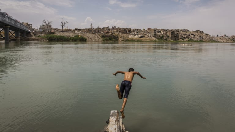 A boy who had been collecting scrap metal cools off with a dip in the Tigris River, across from the destroyed Old City on the western side of Mosul.