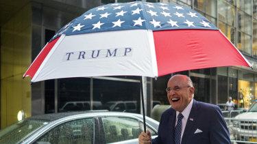 Former New York City mayor Rudy Giuliani leaves Trump Tower bearing an umbrella.