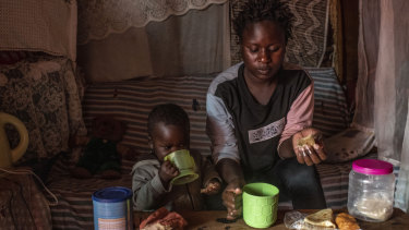 Sharon Mbone has breakfast with her son, who has been ill and taking antibiotics, at home in Kibera, Nairobi.