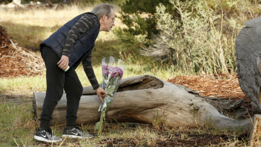 A man lays flowers at the murder scene.