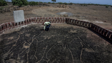 Amateur archaeologist Sudhir Risbud examines a petroglyph of an elephant.