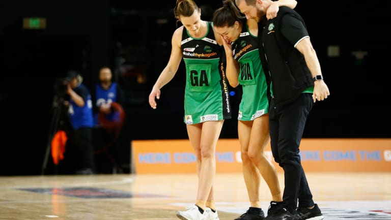 Promising news: Verity Charles (centre) is assisted from the court after hurting her knee last week.