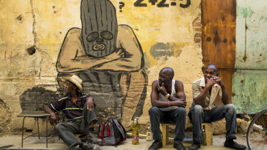 Men sell cooking oil and drink rum in front of a mural by a local street artist in Old Havana.