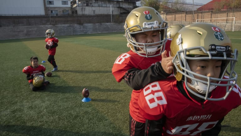 Students help each other put on gridiron helmets.