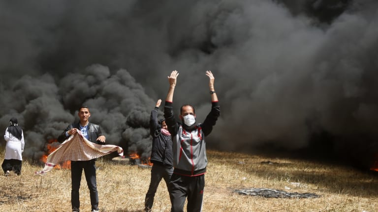 Palestinian protesters call others to bring more tyres to burn during clashes with Israeli troops along Gaza's border with Israel.
