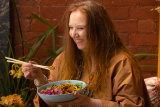Milliner Melissa Jackson eats lunch on the verandah of her Richmond terrace.