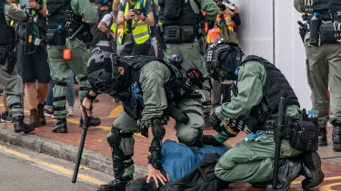 A pro-democracy supporter is detained by riot police during an anti-government rally in Hong Kong, China.