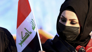 Democracy on the march - again. A woman holds a flag as anti-government protesters gather in Iraq.