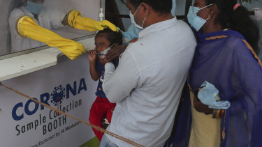 A health worker takes a nasal swab sample from a child at a COVID-19 testing centre in Hyderabad, India.