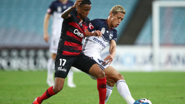 Keisuke Honda of the Victory competes with Keanu Baccus of the Wanderers.