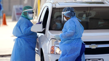 Healthcareworkers administer COVID-19 tests at a drive-through site in San Antonio, Texas.