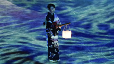 A performer holds a lantern during a moment of remembrance during the closing ceremony.