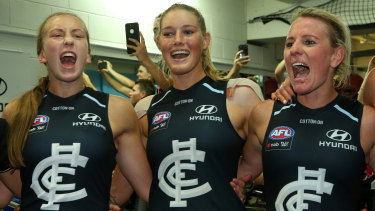 Tayla Harris (centre) and Carlton teammates belt out the club song.