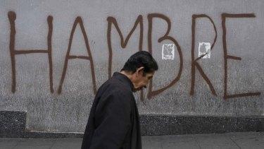 """A man walks past graffiti that reads """"Hunger"""" in Caracas, Venezuela."""