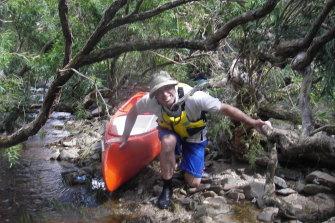 Chad McKenzie dragging his kayak through scrub along the Moorabool River near Meredith in 2016.