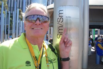 Laurie Smith poses next to his name on the honour roll outside Stadium Australia.