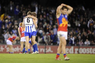 Dejected Lions players look on as the Roos celebrate the win.