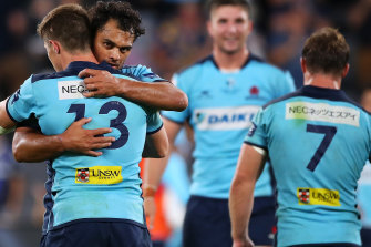 Relieved Waratahs players celebrate their first win of the season on Friday night.