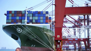 A ship hauls containers at a container port in Qingdao in eastern China's Shandong province.