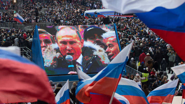 Attendees wave Russian flags in support of President Vladimir Putin as he speaks on screen during a pre-election rally at Luzhniki stadium in Moscow in March.