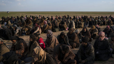Men wait to be screened after being evacuated out of the last territory held by Islamic State militants, near Baghouz, eastern Syria.