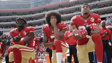 Iconic moment: Kaepernick, centre, takes a knee during the US national anthem in 2016.