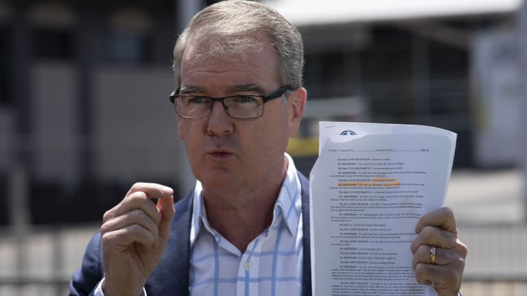 Labor leader Michael Daley holds a transcript of a testimony stating that 'all of the seats are flammable'.