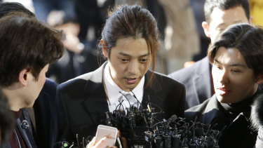 Jung Joon-young, centre, is accused of having secretly filmed himself having sex with about 10 women and sharing the footage with friends by a mobile messenger app.